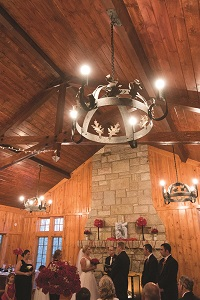a wedding taking place in the rustic lodge with wood ceiling and rock fireplace