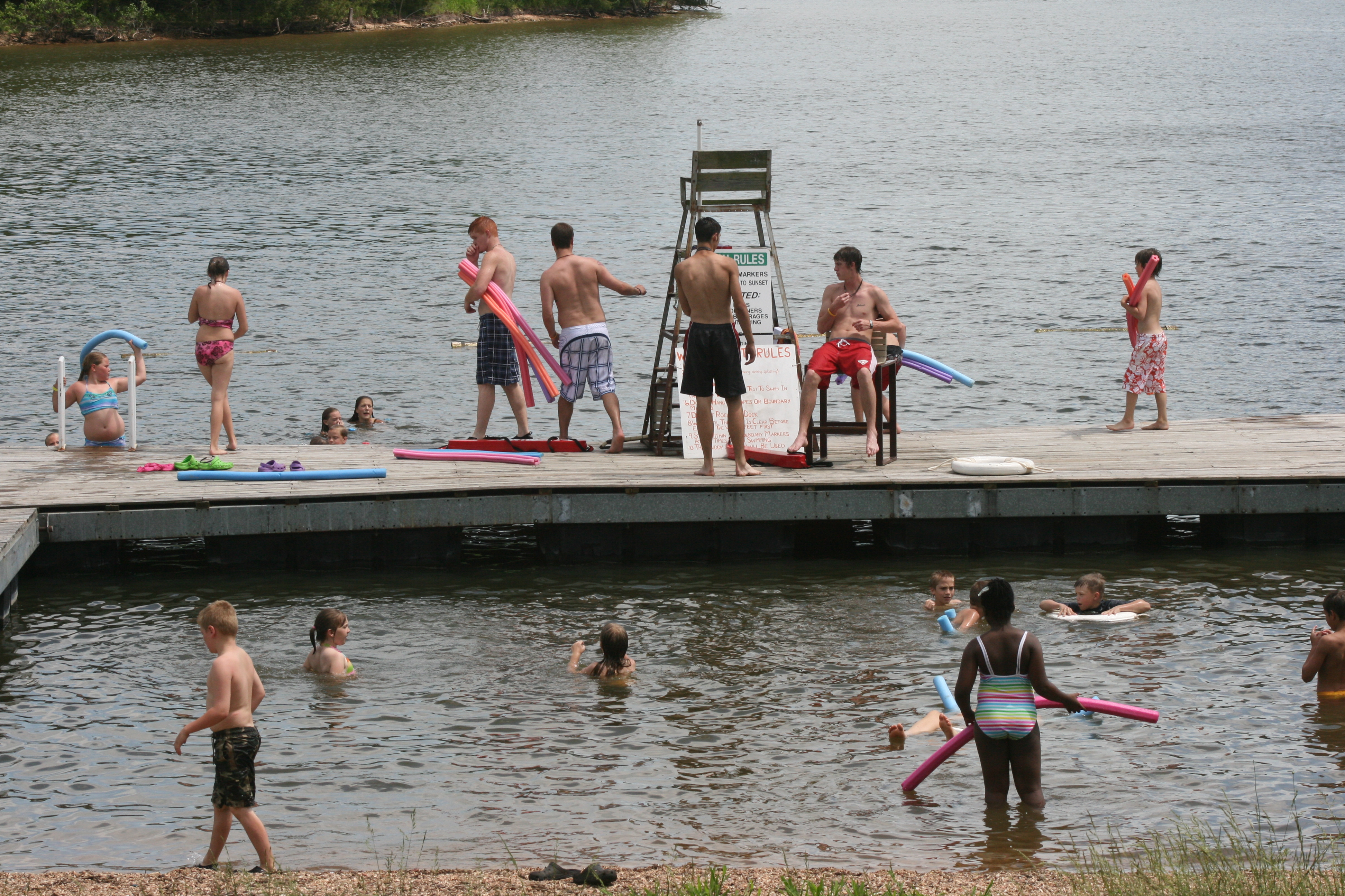 kids on the swim dock and swimming in the lake