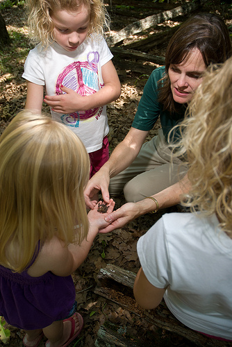 a naturalist showing a small child something in her hand