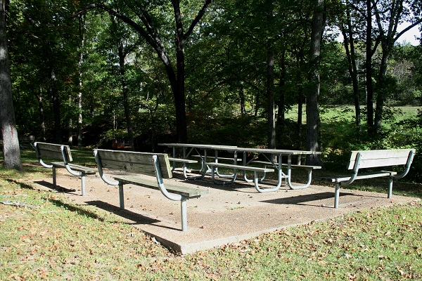 group picnic area with two tables and three separate benches on a concrete pad