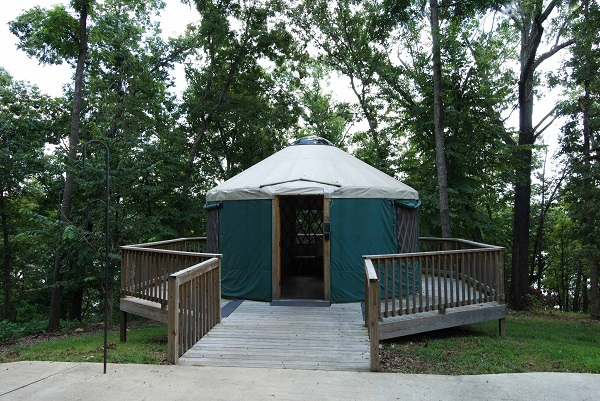 exterior of yurt with a deck beneath large shade trees