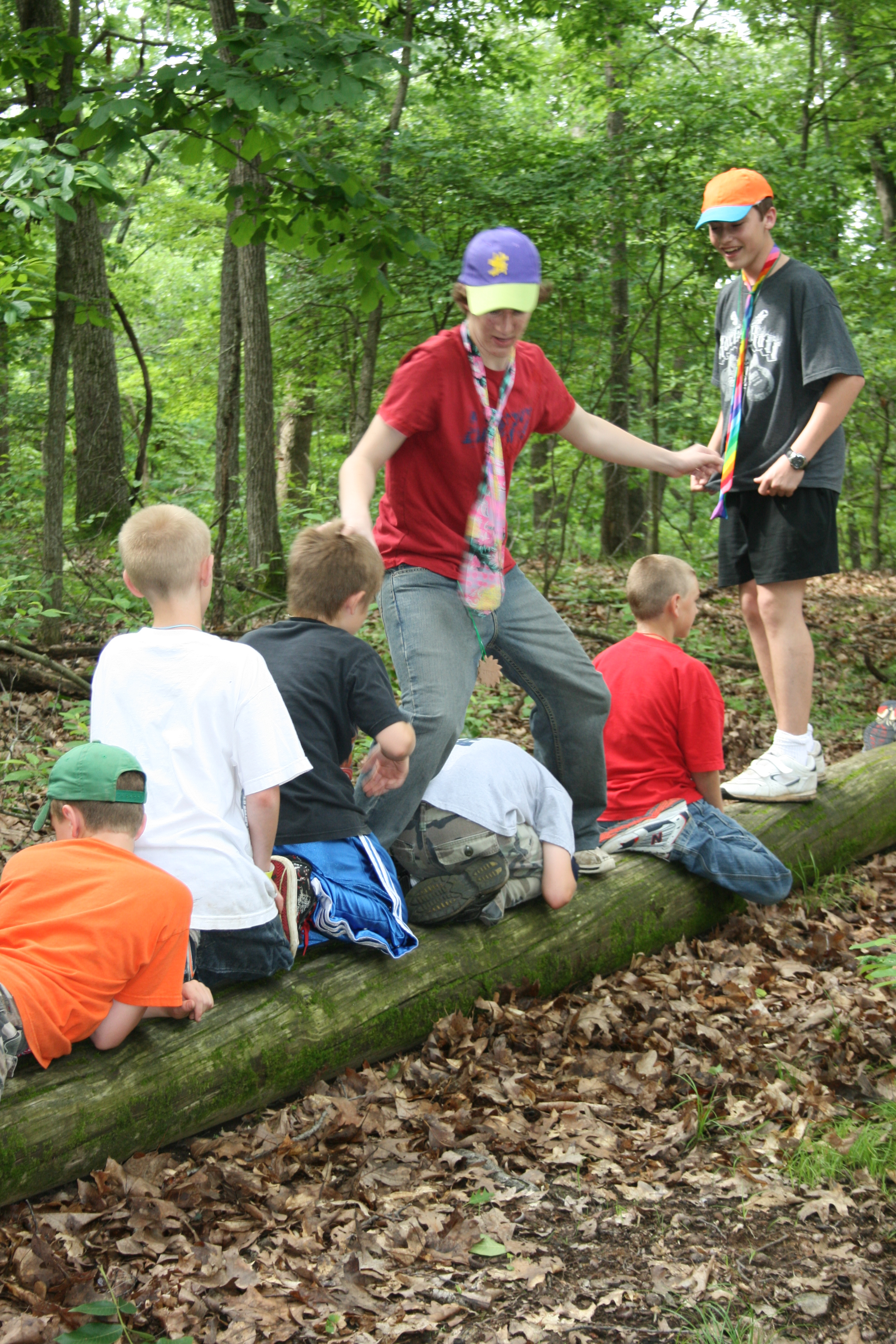 Kids on a log work on a team building activity