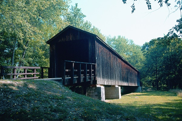wooden covered bridge spanning a grassy area