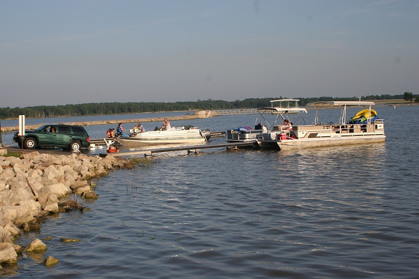 a boat unloading on the boat ramp while a pontoon boat is pulled up to the dock