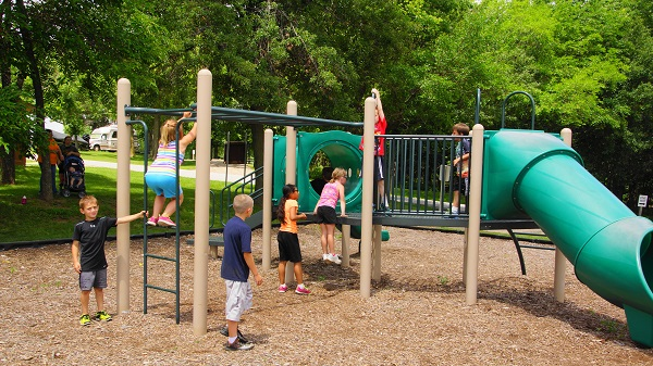 kids playing on the playground equipment with monkey bars and slides