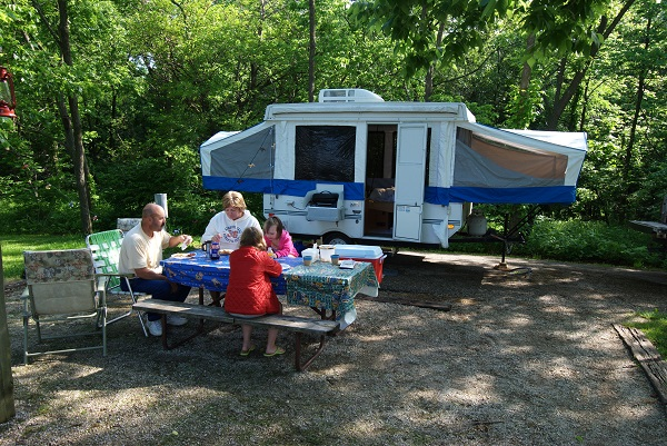family sitting at picnic table in front of camper