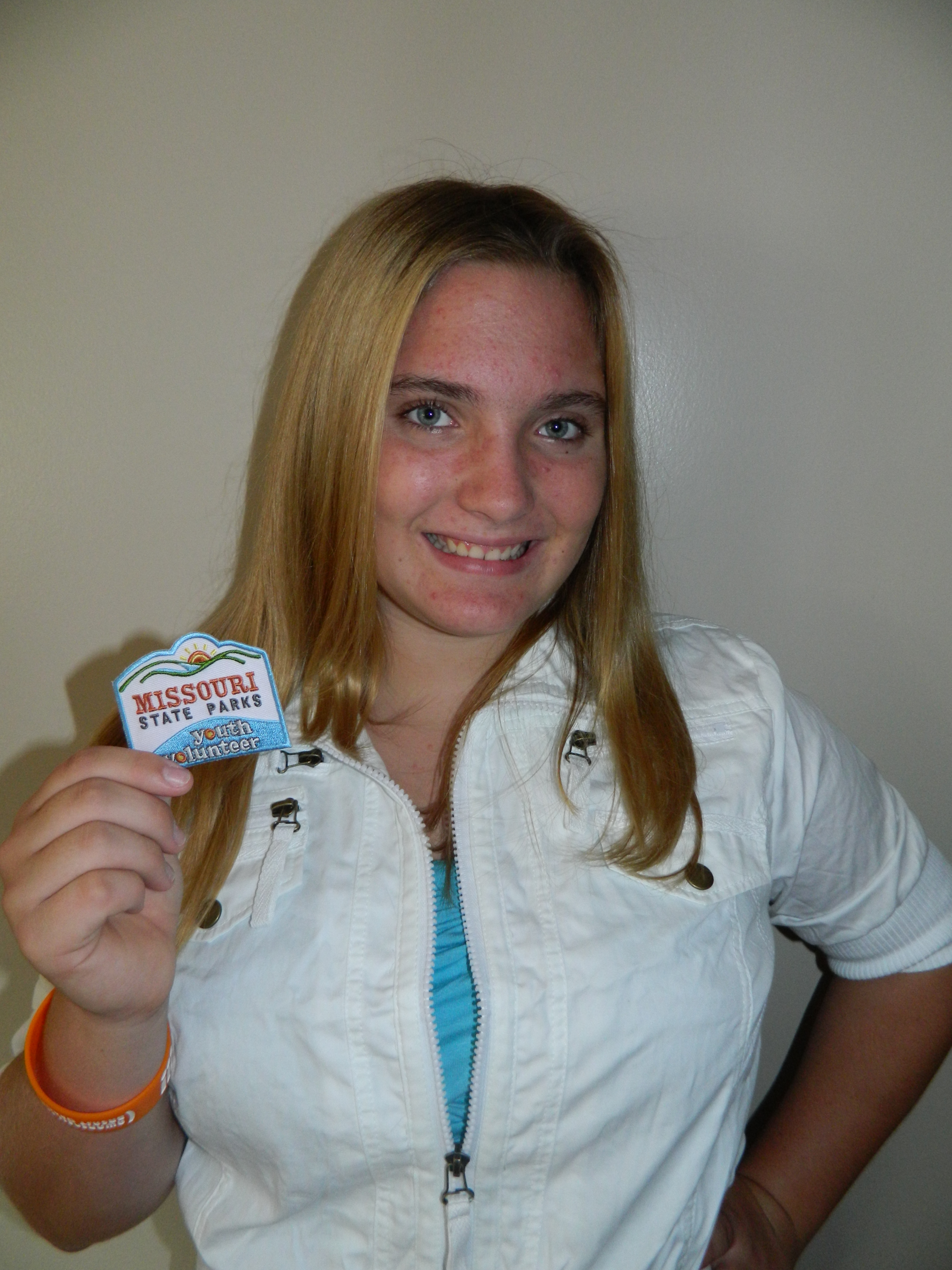 a young girl showing off the patch she earned