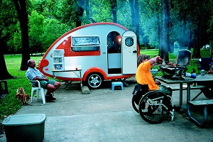 Man in wheel chair cooking over a camp stove with camper and another man in background