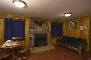 fireplace, dining table and futon inside a cabin
