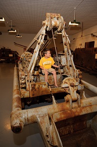 a kid sitting on a piece of the  old mining equipment