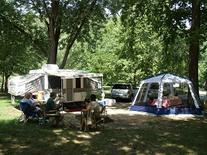 people sitting at the campsite with a camper and tent behind them