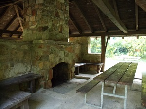 rock fireplace and table inside a shelter