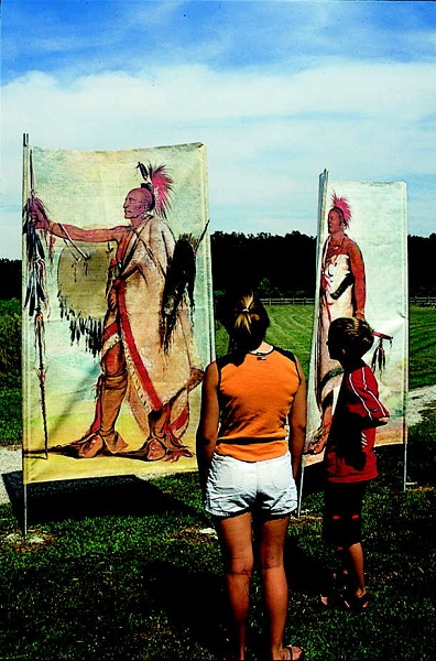 two kids look at flags that show images of Osage Indians