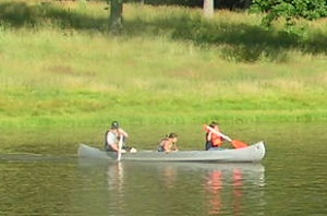 three people in a canoe on the lake