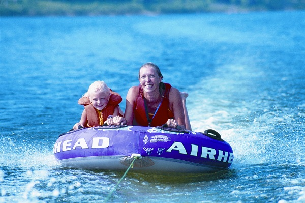 a mother and daughter being pulled on a tube on the lake