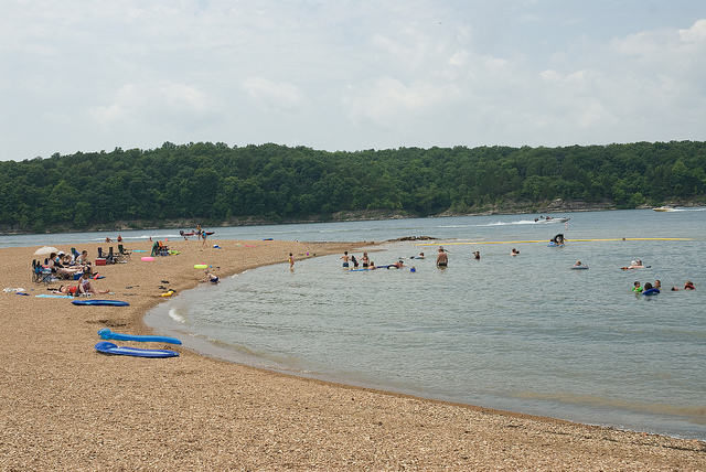 people on the beach and swimming in the lake