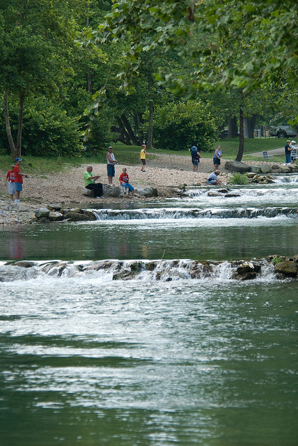 small cascades of water flowing down the river with people fishing on the bank