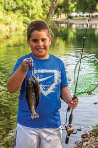 a kid holding up a fish he caught