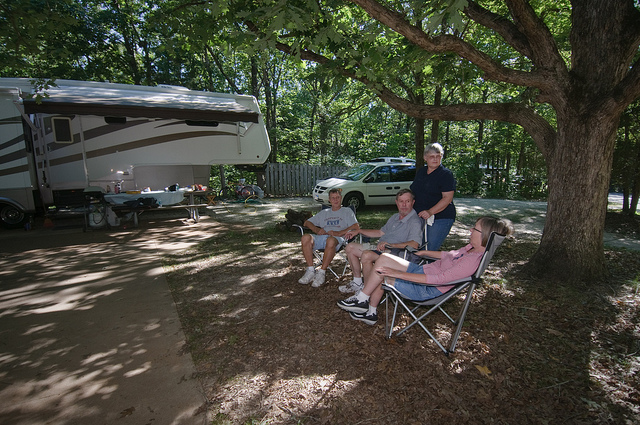 two couples sitting in lawn chairs by their camper