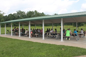 a large group is gathered for a program under one of the park's picnic shelters
