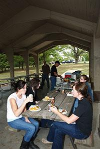 severl people enjoying a meal under one of the picnic shelters