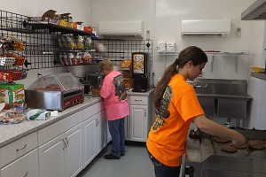 two women preparing food inside the concession stand