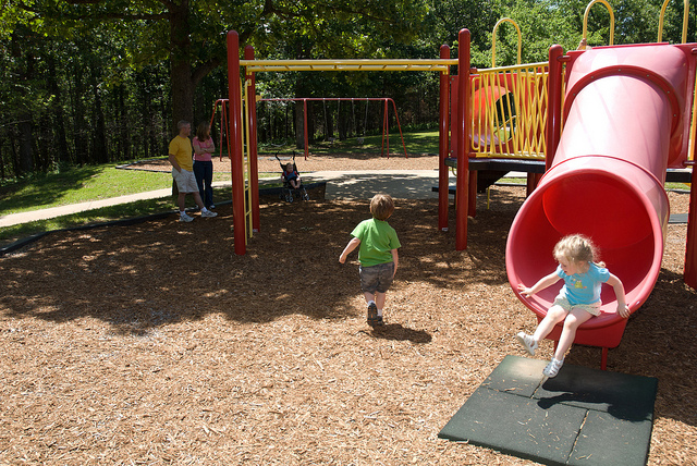 toddlers playing on playground equipment with slides and monkey bars