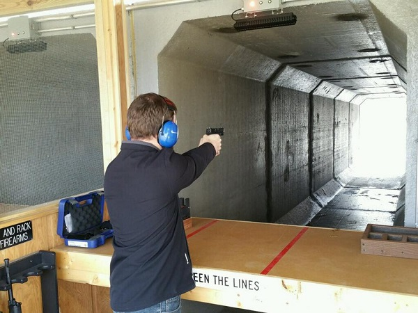 A man shooting a gun at a target at the shooting range.