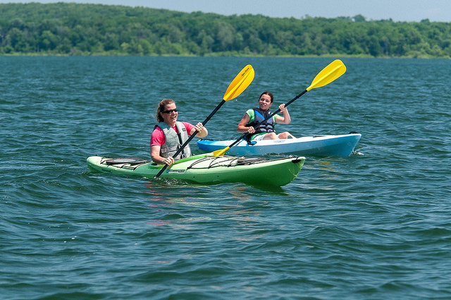 two woman in kayaks on a lake