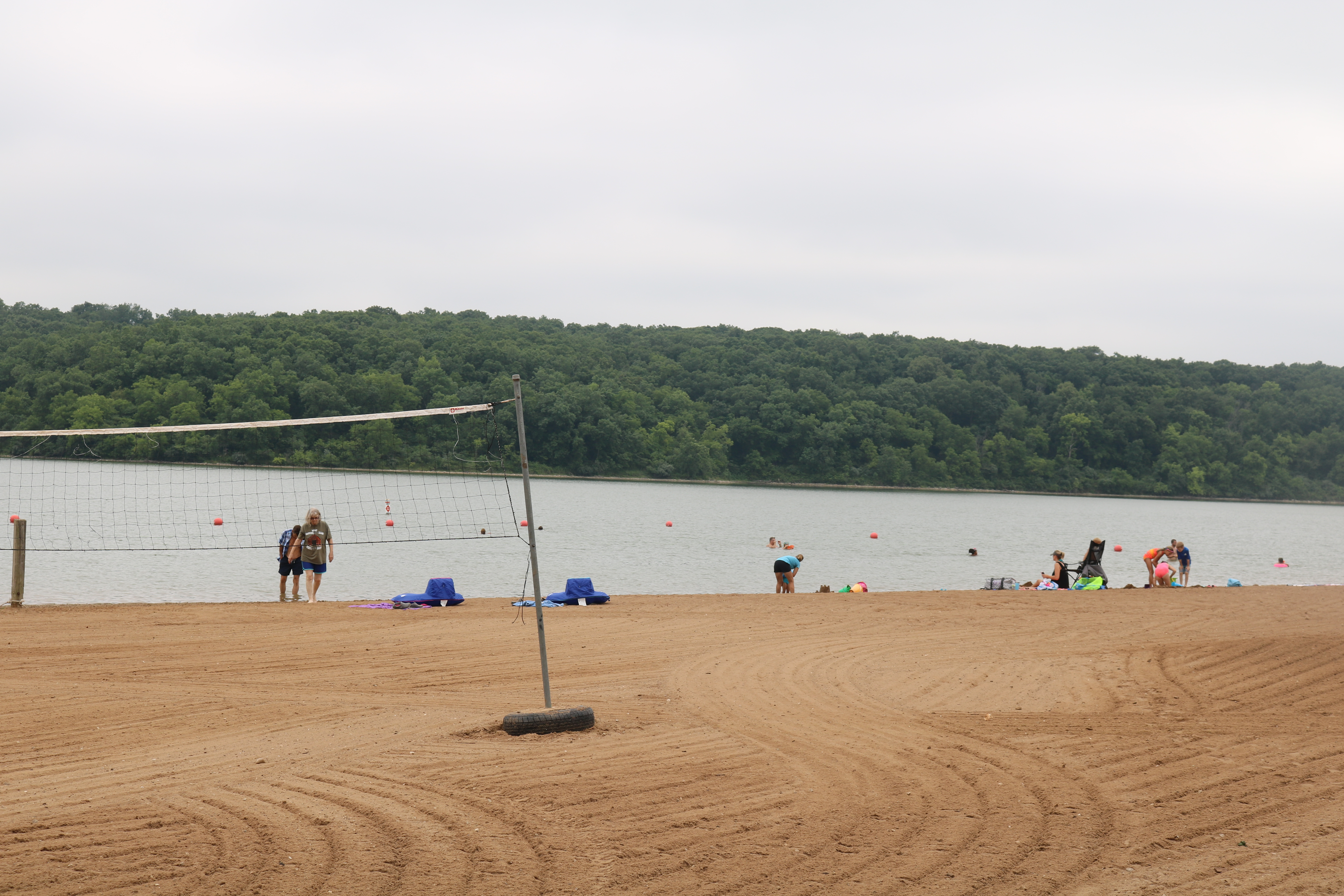 a volleyball net and people swimming in the lake
