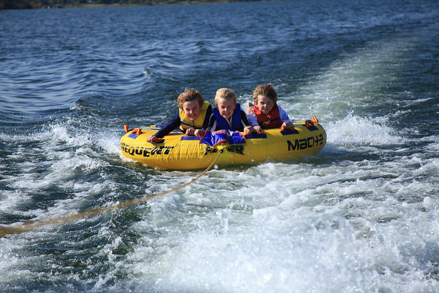 three kids on a tube on the lake