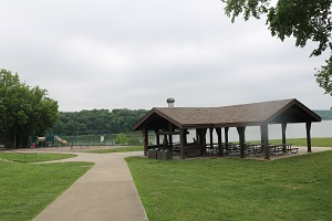 a sidewalk leads to the picnic shelter and playground next to the lake
