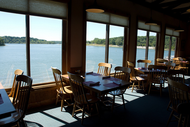 tables and chairs are lined up next to windows that overlook the lake