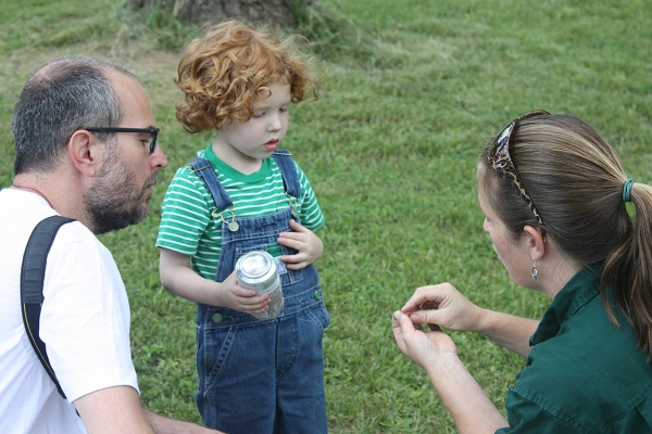 a naturalist shows a small child something in her hands