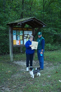 a couple with their dog looking at a park brochure