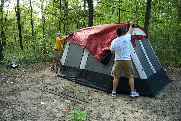 two men putting the fly on their tent