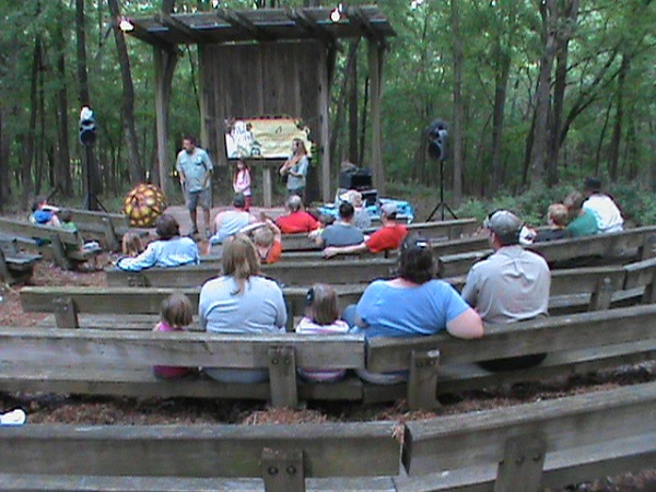 people sit on the wooden benches at the amphitheater listening to a program