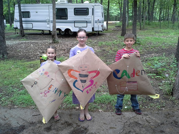 three kids showing off kites they made