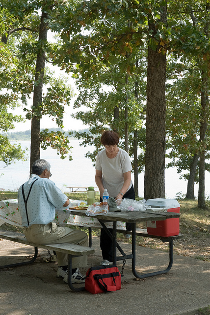 a couple enjoys lunch at a picnic table close to the lake