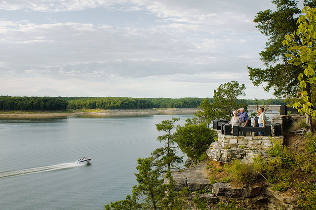 people standing on a rock overlook watching a boat go by on the lake below