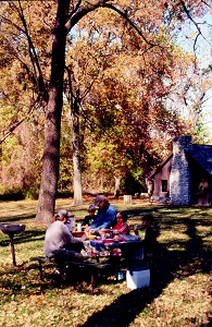 a family enjoys a picnic luncg at a picnic table under large shade trees