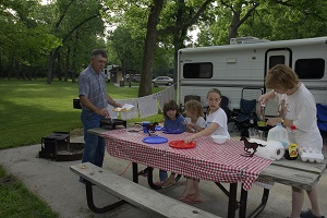 a family preparing to eat on the picnic table outside their camper