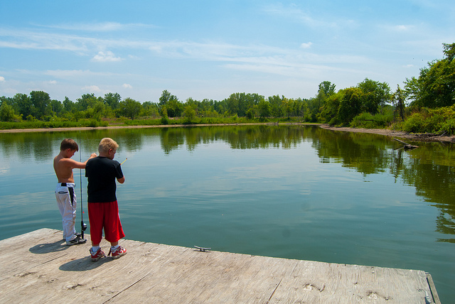 two boys fish from a dock