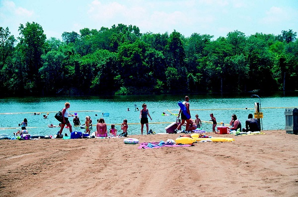 several people sitting on the beach and swimming in the lake