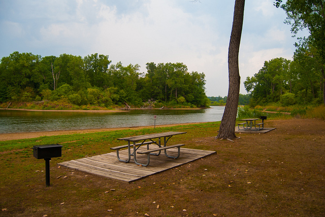 a picnic table on a wood platform and a grill close to one of the lakes