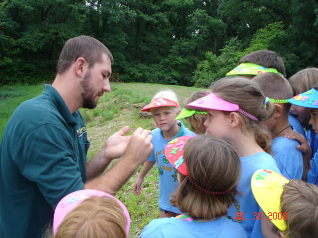 a naturalist showing a group of kids something in his hand