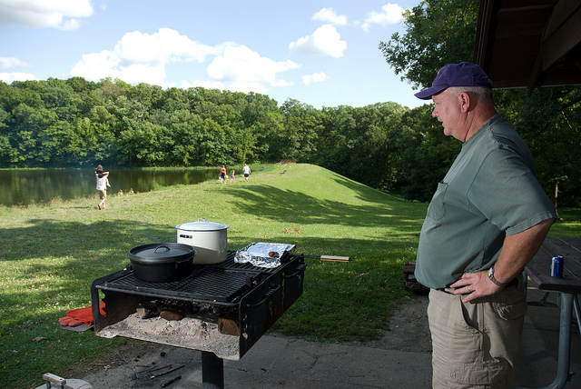 a man watching food cook on a grill