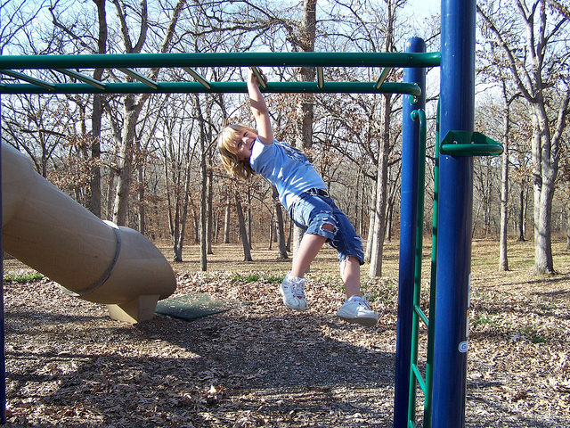 a girl on the monkey bars