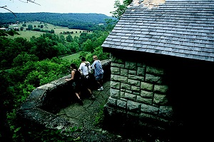 three people standing at a stone shelter overlooking the surrounding valley