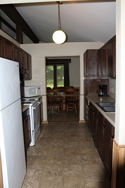 kitchen with stove, refridgerator and sinks inside a cabin